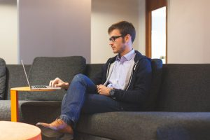 Freelancer / Selbstständiger / Unternehmer der auf einem Sofa arbeitet